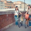 Two Beautiful Women Walking in the City with Bicycles and Bags — Stock Photo #13357408