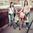Two Beautiful Women Walking in the City with Bicycles and Bags — Stock Photo #13357421