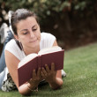 Young beautiful woman lays on green field and reads book. — Stock Photo #13357654
