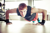 Strong, handsome man doing push-ups in a gym as bodybuilding exe — Stock Photo