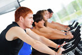 Group of five in the gym, exercising their legs doing car — Stock Photo