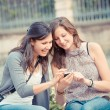 Two shopping girls in park with a mobile phone — Stock Photo