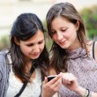 Stock Photo: Two shopping girls in park with a mobile phone