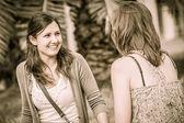 Iki genç kadın parkta bir bankta — Stok fotoğraf