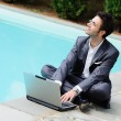 Young Businessman with Computer next to Swimming Pool — Stock Photo #14503657
