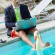 Stock Photo: Funny Young Businessmwith SwimmingTrunks next to Pool