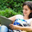 Young woman using tablet outdoor laying on grass — Stockfoto