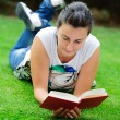 Young beautiful woman lays on green field and reads book. — Stock Photo #14504161