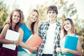Portrait happy young students in park — Stock Photo