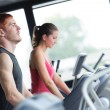 Running on treadmill in gym or fitness club - group of women and - Stock Photo