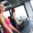 Running on treadmill in gym or fitness club - Stock Photo