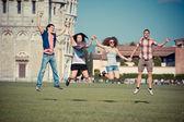背景にピサの斜塔とジャンプの友人のグループ — ストック写真