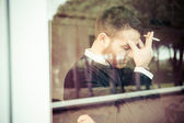 Worried man smoking a cigarette close to the window — Stock Photo