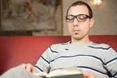 年轻的成年男子被吸收在读一本书 — 图库照片