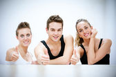 Three Smiling Persons after Fitness Exercises with thumbs up — Stock Photo