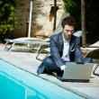 Young Businessman with Computer next to Swimming Pool — Stock Photo #20392259