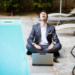 Young Businessman with Computer next to Swimming Pool — Stock Photo #20392401