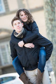 Happy couple piggyback hugging in wintertime park love smiling f — Stock Photo