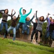 Group of Happy College Students Jumping at Park — Stock Photo #21681659
