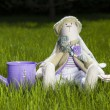 Toy rabbit sitting on grass with can — Stock Photo #12250653