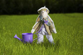 Toy rabbit with can on grass — Stock Photo