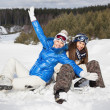 Foto Stock: Two girls with snowboards sitting on snow and laughing