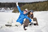 两个女孩与滑雪板在雪地上坐着笑着 — 图库照片