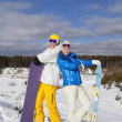 Stock Photo: Couple with snowboards in their hand standing on a hillside