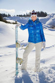 Young woman standing with snowboard in her nand and smiling — Стоковое фото