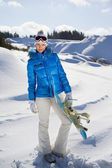 Pretty woman standing with snowboard in her nand and smiling — Stock Photo