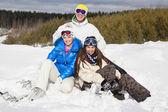 Unga sitter på snön och ler — Stockfoto