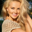 Closeup portrait of smiling blonde girl keeping her hair with ha — Stock Photo #19839629
