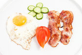 Fried eggs, bacon and vegetables on white background — Stock Photo