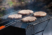 Four Hamburgers on Barbeque Grill — Stock Photo