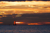 Sailing boat silhouette at sunset in sea — Stock Photo