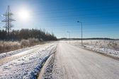 Solen på elektriska kraftledningar nära road — Stockfoto