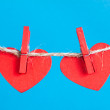 Hearts on clothesline with clothespins, blue background — Stock Photo #19496189