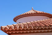 Small statue on the red tiled roof — Stock Photo