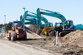 Excavators and asphalt compactor truck — Стоковое фото