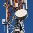 Stock Photo: Communications tower with antennas on blue sky