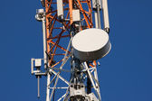 Communications tower with antennas on blue sky — Stock Photo