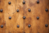 Wood and metal door with metallic spikes looking worn and grungy — Stock Photo