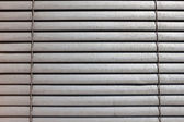 Grey shutters over a shop window — Stock Photo