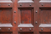 Wood and metal door with metallic spikes looking worn and grungy. — Stock Photo