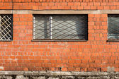 Brick wall with metal window bars — Stockfoto