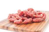 A heap of mini Salamis on wooden board — Stock Photo