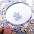 Magnifying Glass and Single Puzzle Piece — Stock Photo