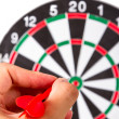 Stock Photo: Hand Holding Arrow and Throwing Dart Board