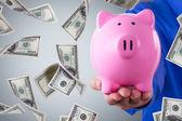 Biznesmen trzyma skarbonkę i banknotów dolara pływające — Zdjęcie stockowe