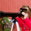 Little girl using a telescope — Stock Photo